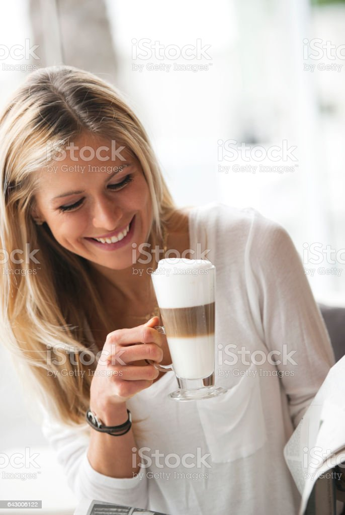 Woman with coffee reading newspaper stock photo