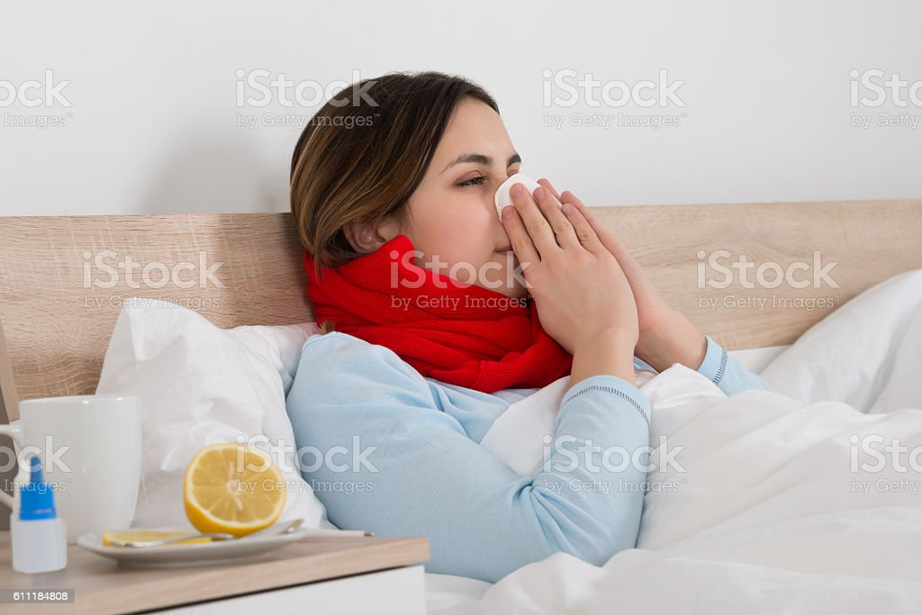 Woman With Cold Blowing Her Nose stock photo