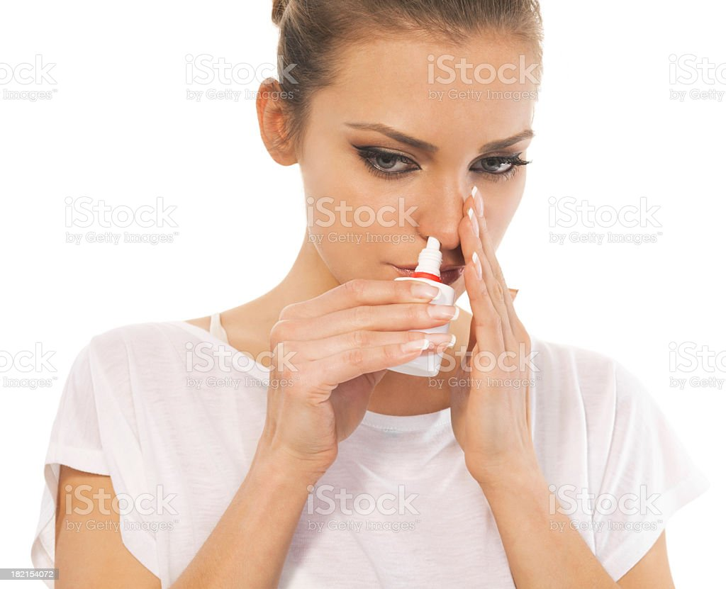 Woman with cold using nasal spray stock photo