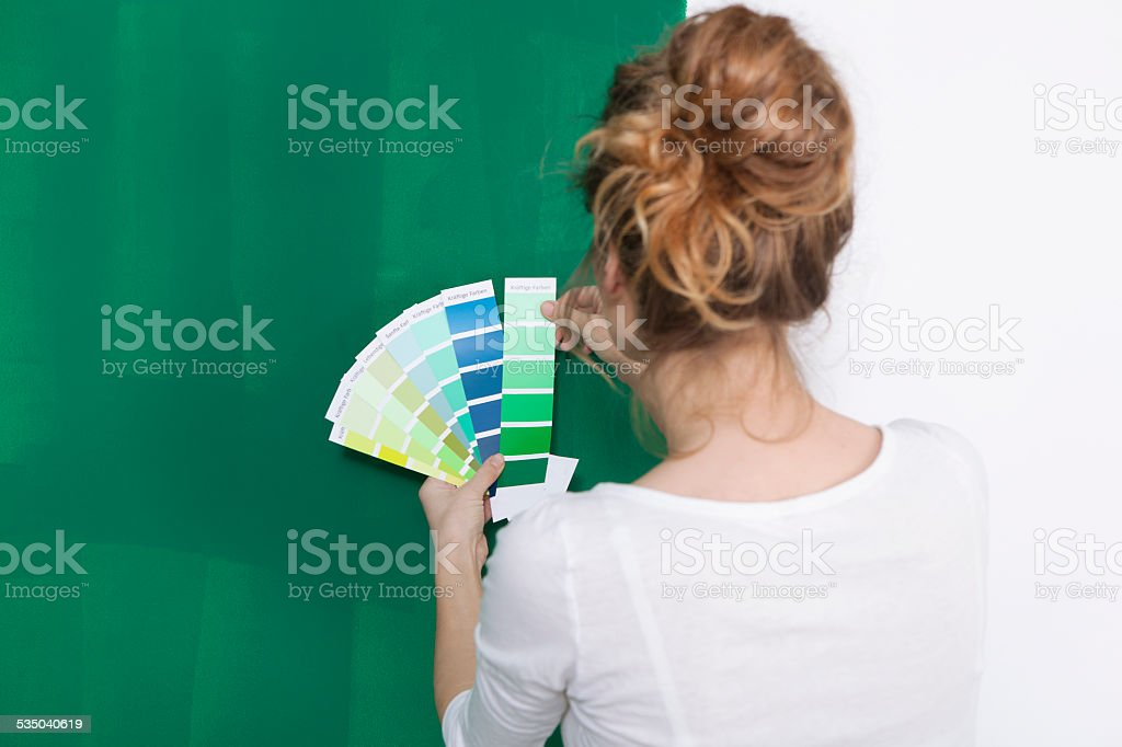 Woman with color plates in front of a green wall stock photo