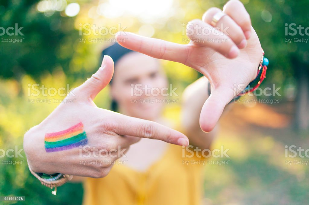 Woman with colored flag on hand making finger frame stock photo