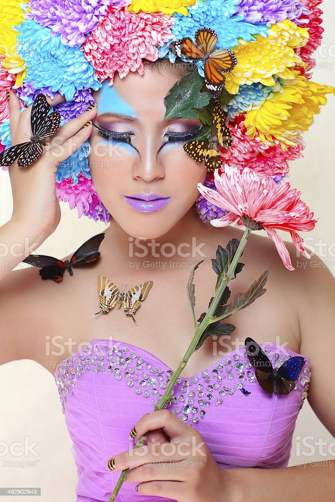 woman with colorful flower hat and butterfly stock photo