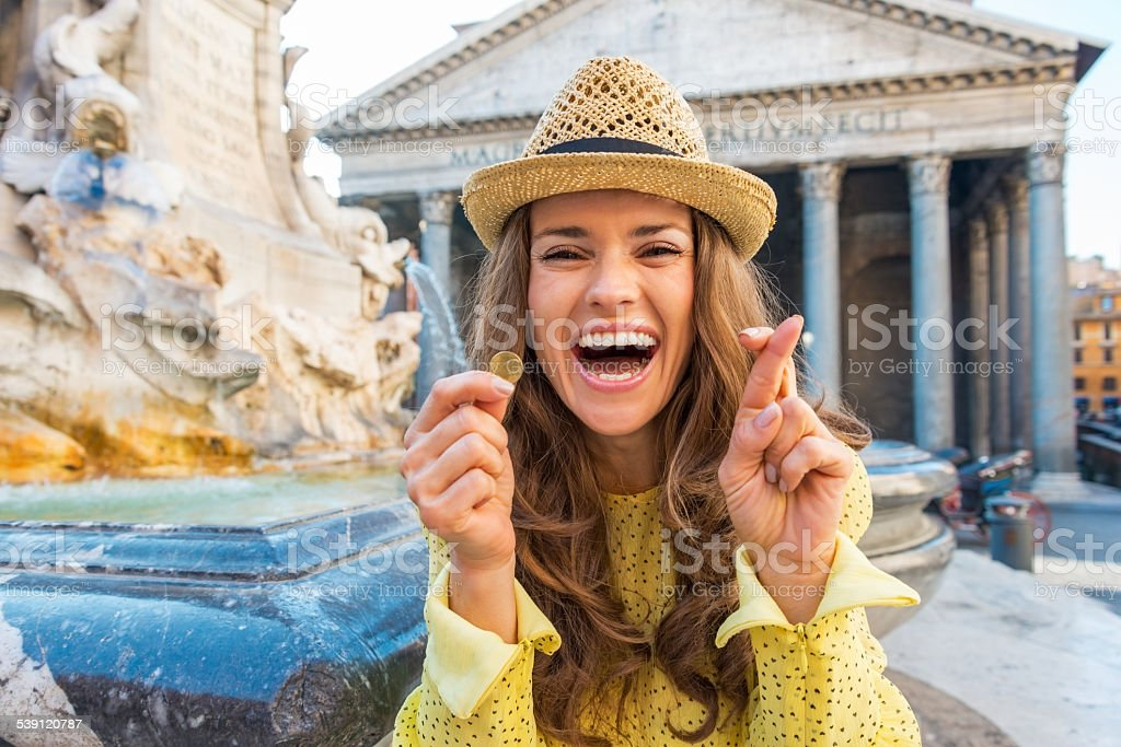 Woman with crossed fingers and coin near fountain in rome stock photo