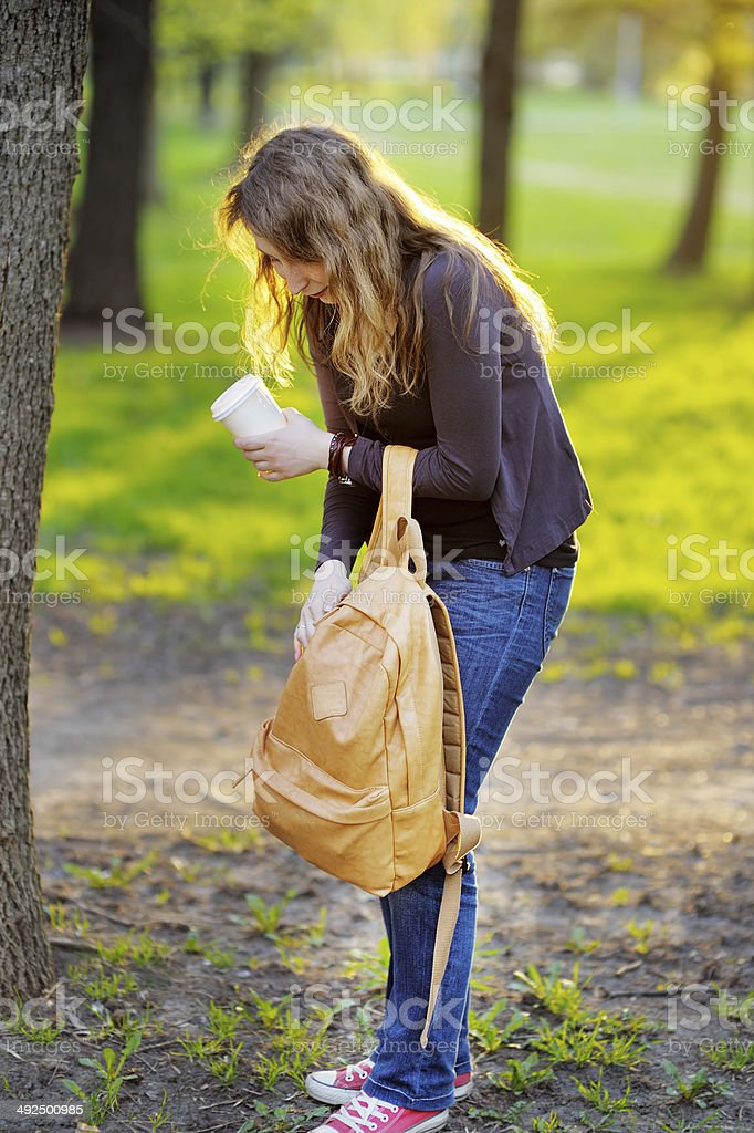 Woman with cup of coffee and bag in park stock photo