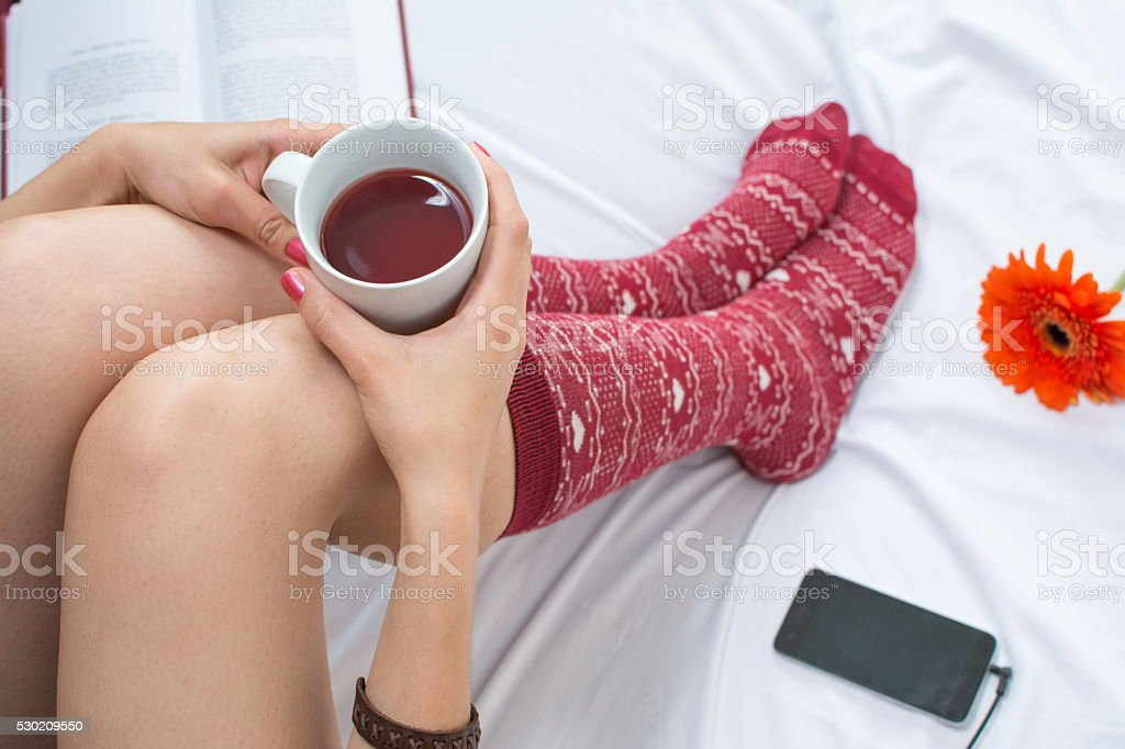 Woman with cup of tea in bed stock photo
