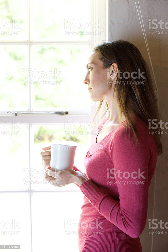 Woman with cup of tea looking out window stock photo