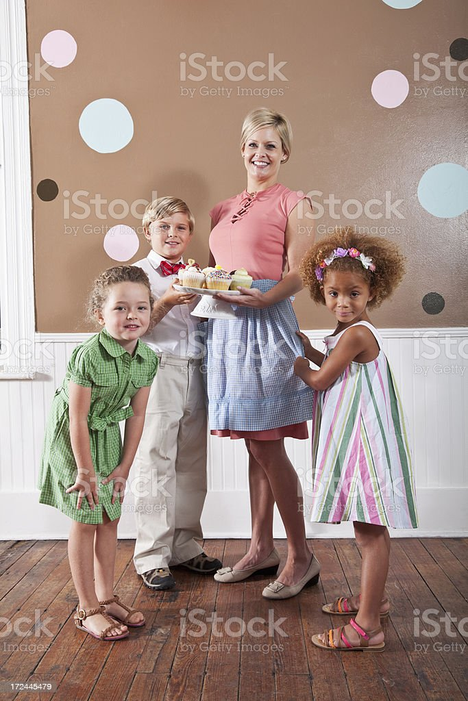 Woman with cupcakes surrounded by children stock photo