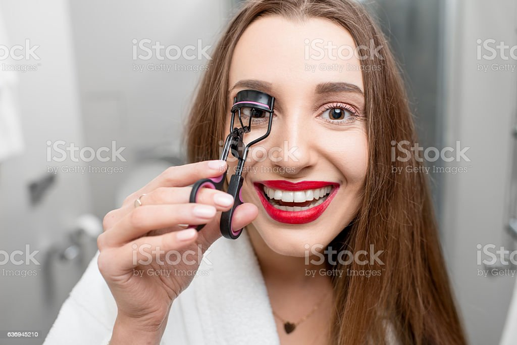 Woman with curler tool for eyelashes stock photo
