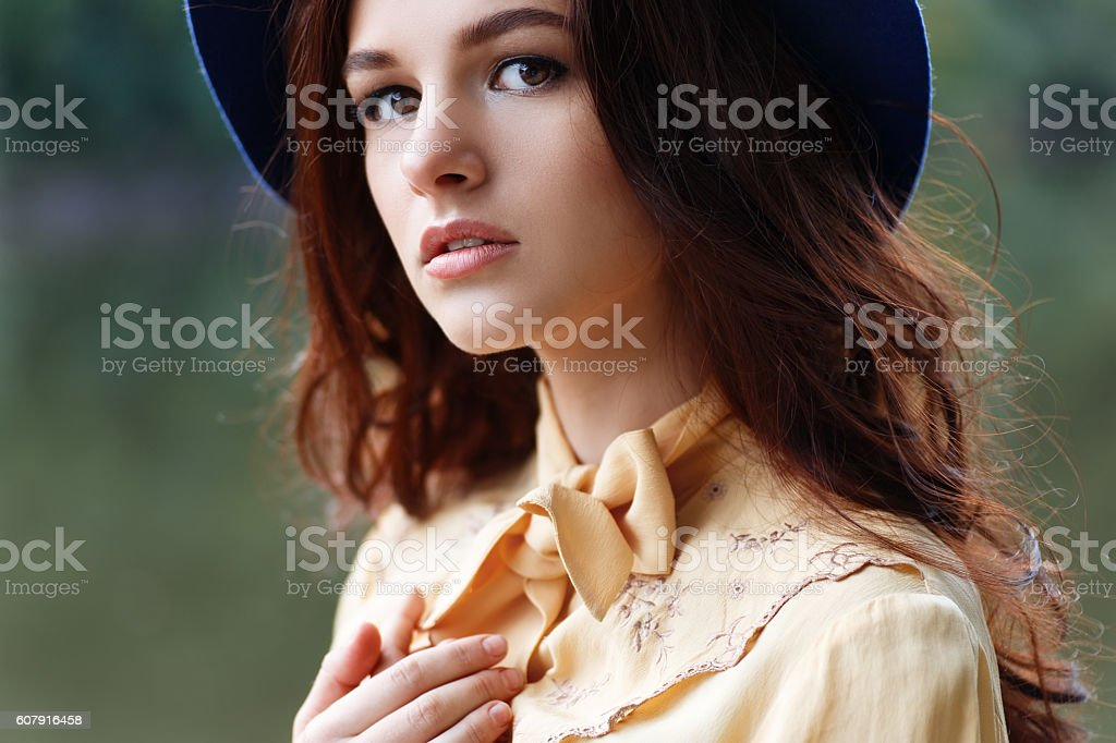 woman with curly hair and floppy hat stock photo