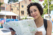 Woman with curly hair holding map