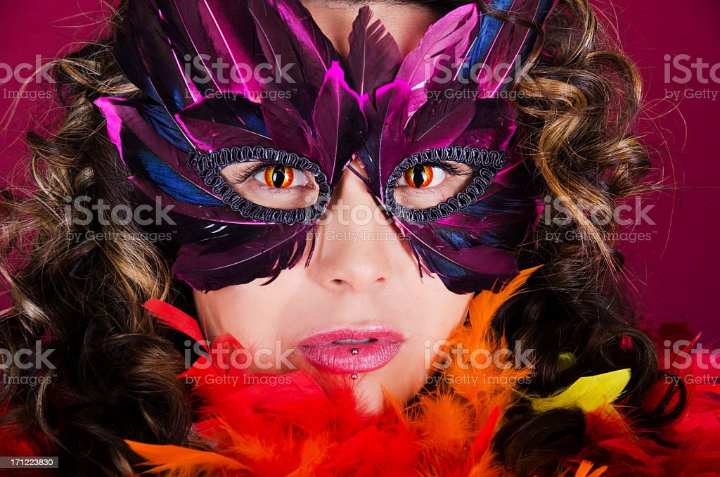 Woman with curly hair, mask and snake contact lenses. stock photo