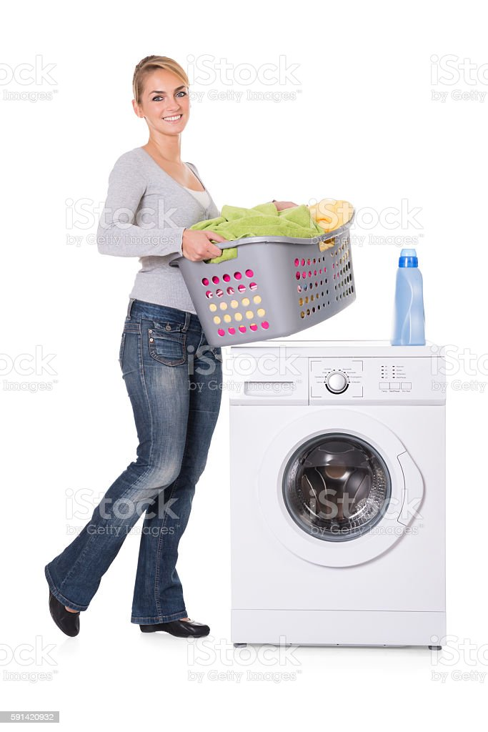 Woman With Detergent And Laundry Standing By Washing Machine stock photo