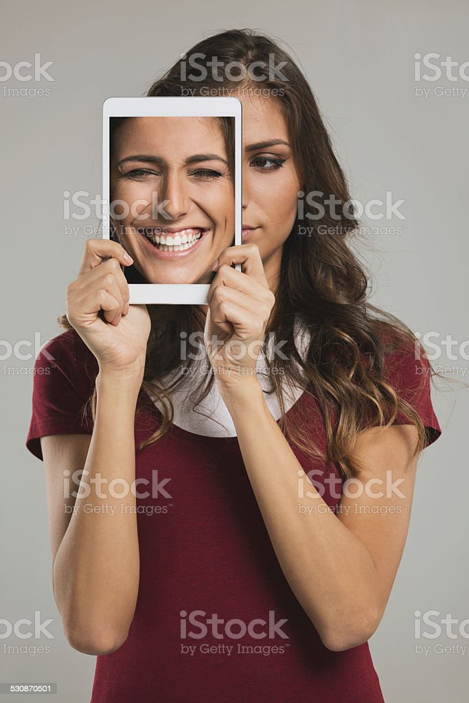 Woman with digital tablet and different faces stock photo