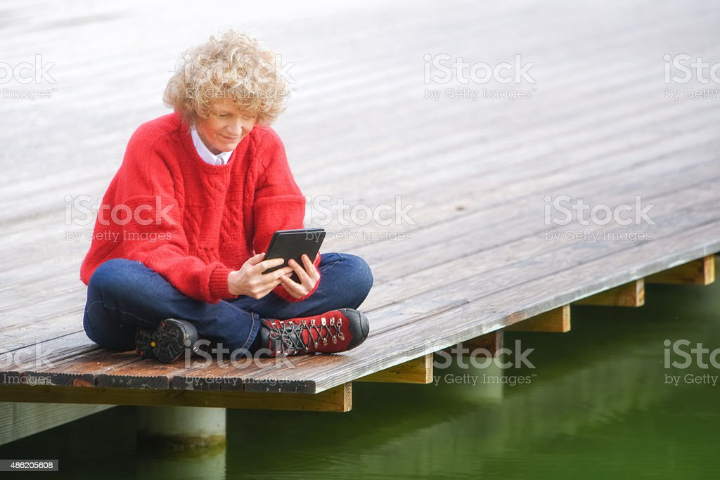 Woman with digital tablet by lake stock photo