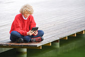 Woman with digital tablet by lake