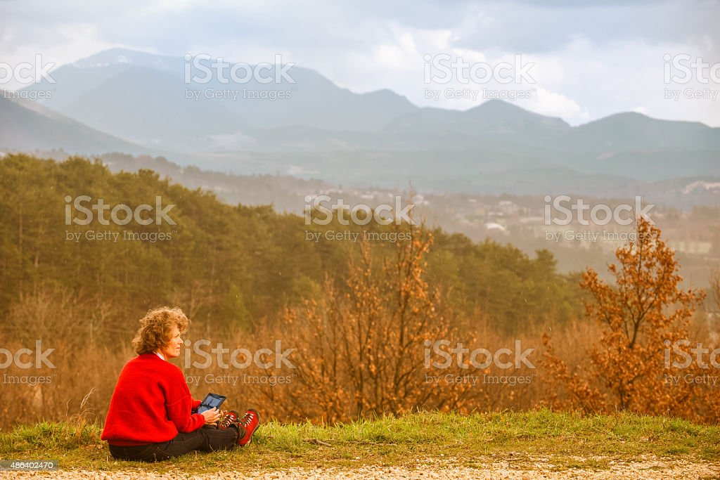 Woman with digital tablet in autumn countryside stock photo