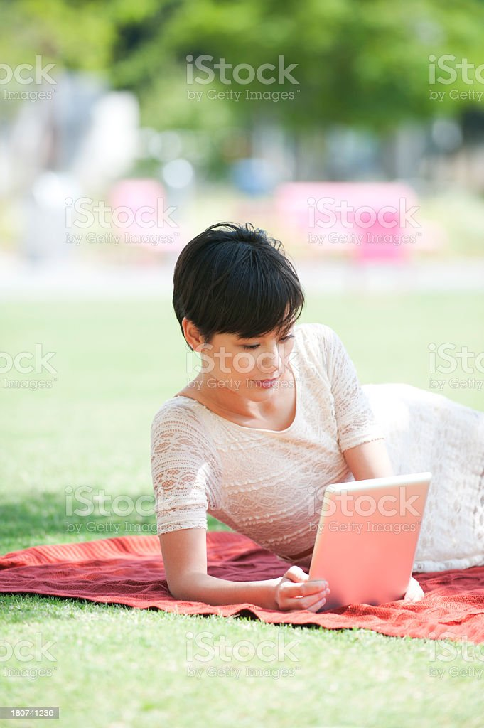 Woman with digital tablet in the park royalty-free stock photo