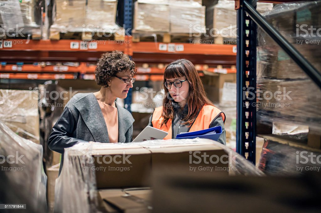 Woman with digital tablet in warehouse talking to worker stock photo