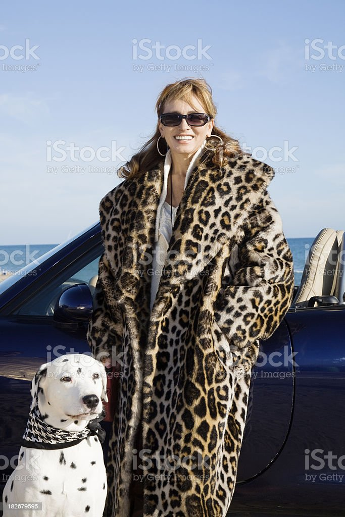 Woman with dog, convertible and luxury coat portrait stock photo