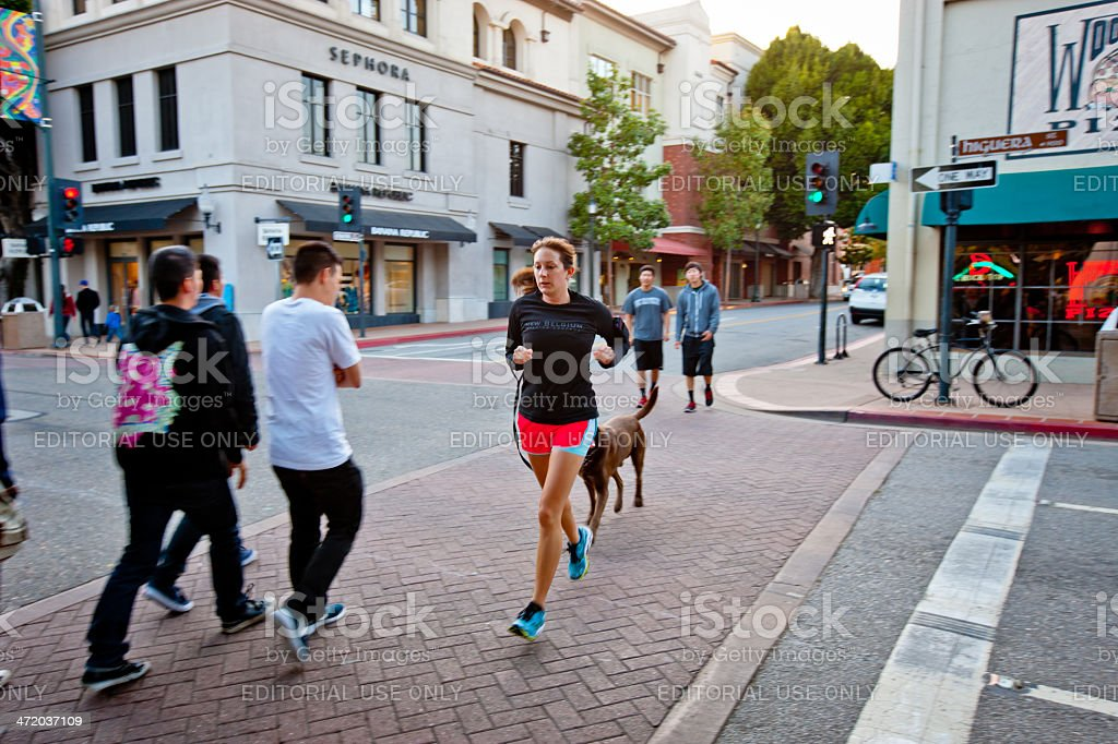Woman with dog crossing street jogging stock photo