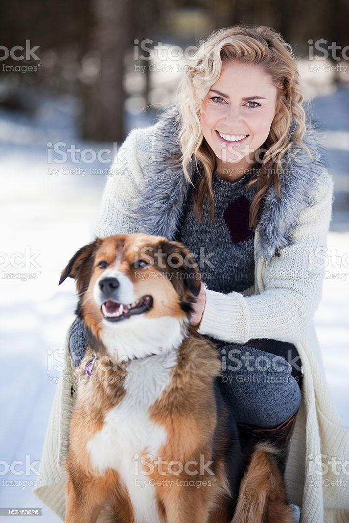 Woman with dog in snow stock photo
