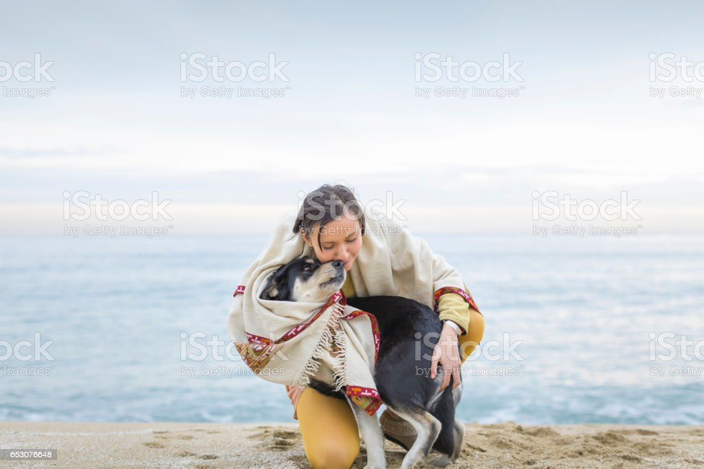 Woman with dog on the beach stock photo