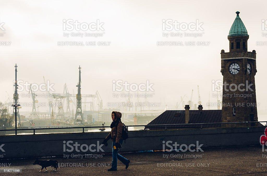 Woman with dog walking next to Landungsbruecken, Hamburg, Germany stock photo