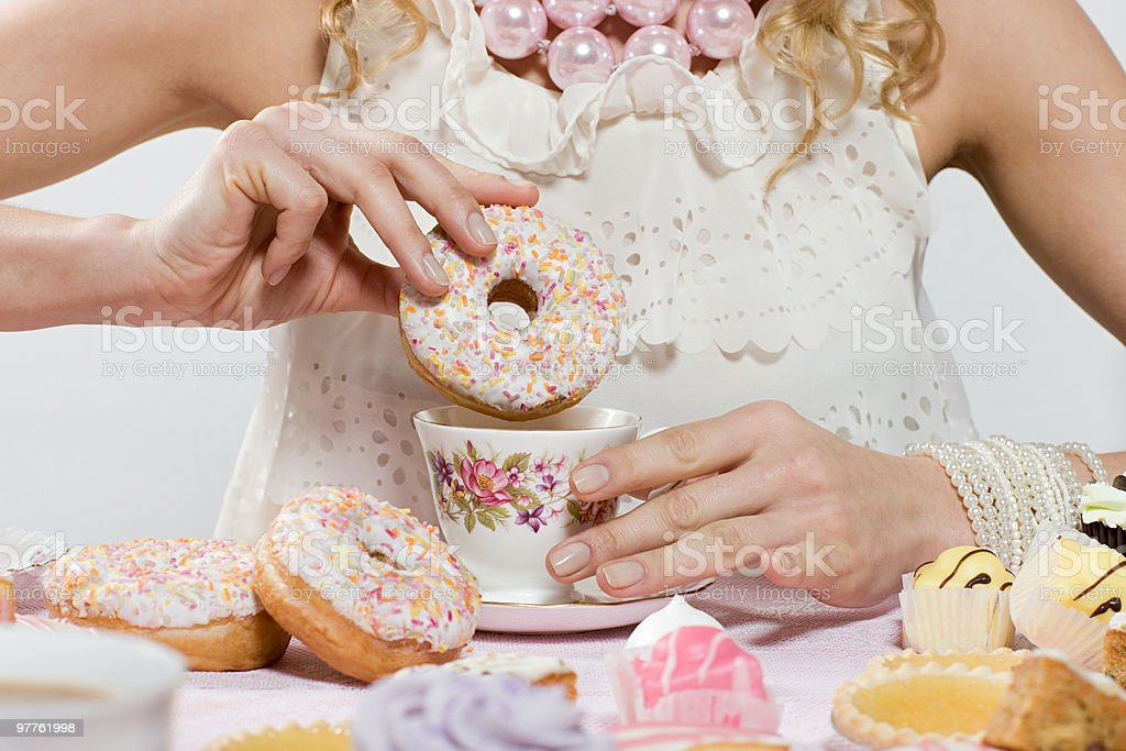 Woman with doughnut and cup of tea stock photo