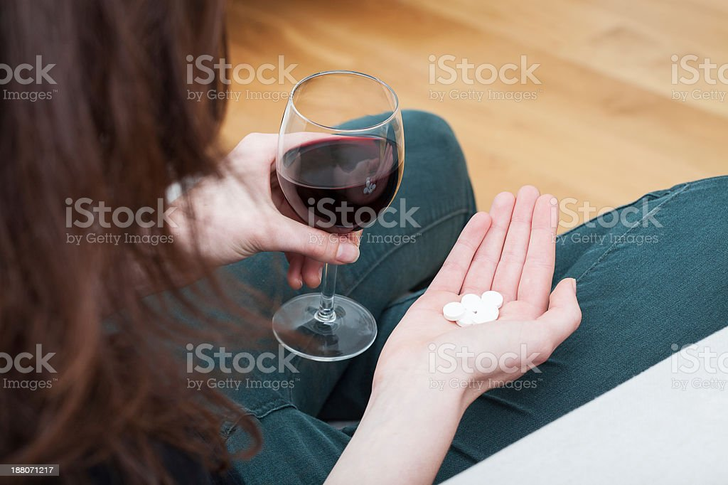 Woman with drugs and glass of wine stock photo