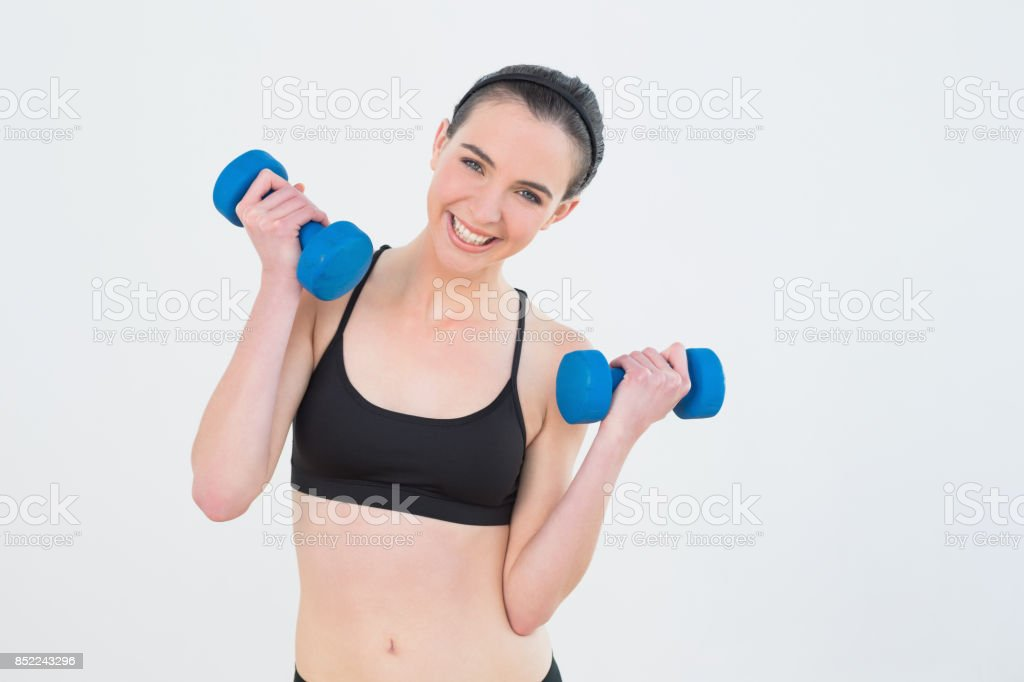 Woman with dumbbells against wall at fitness studio stock photo