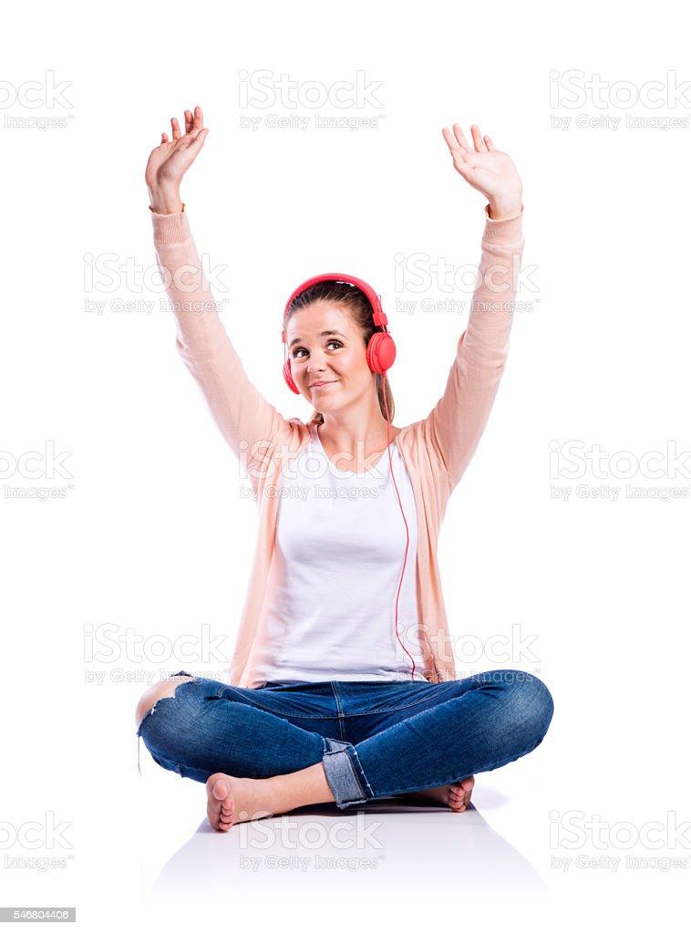 Woman with earphones sitting on the floor, studio shot, isolated stock photo