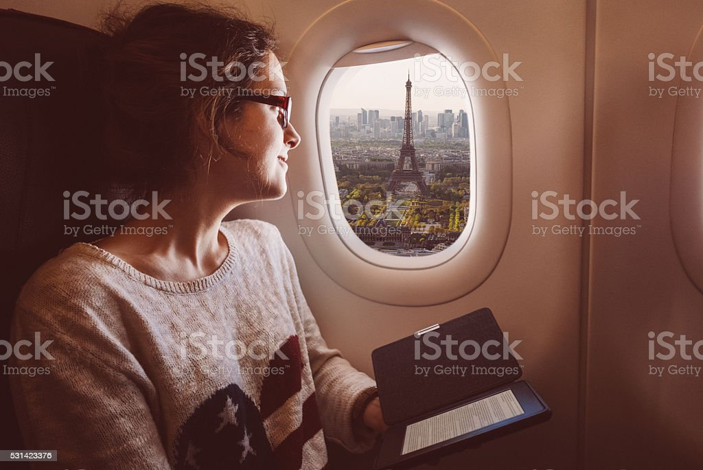 Woman with e-book in the airplane travelling to Paris stock photo