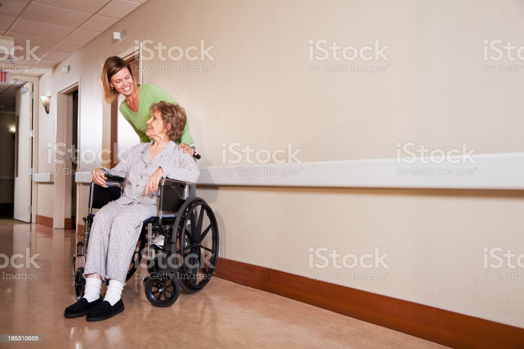 Woman with elderly mother in wheelchair stock photo