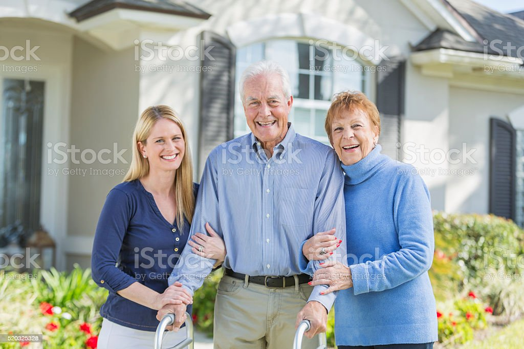 Woman with elderly parents standing in front of house stock photo
