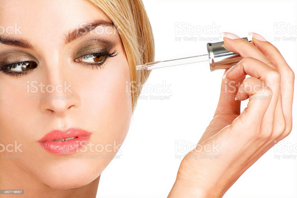 Woman with elegant makeup applying serum treatment stock photo