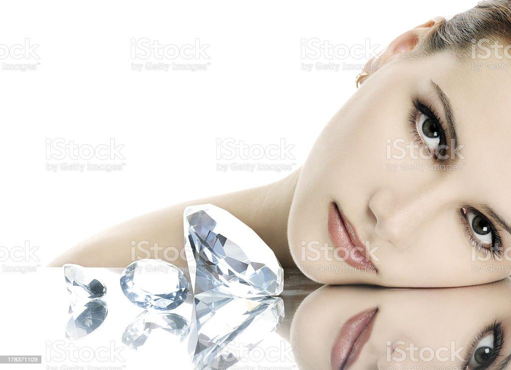 Woman with elegant makeup resting next to shiny diamonds royalty-free stock photo