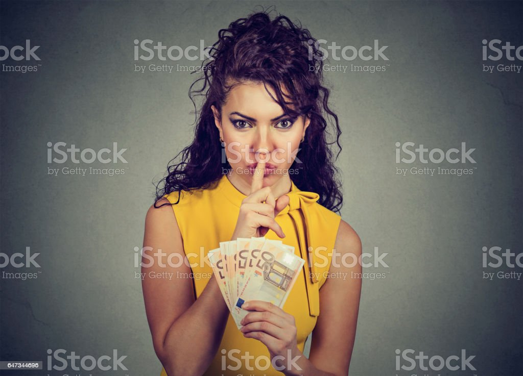 woman with euro money showing shhh sign finger on lips stock photo