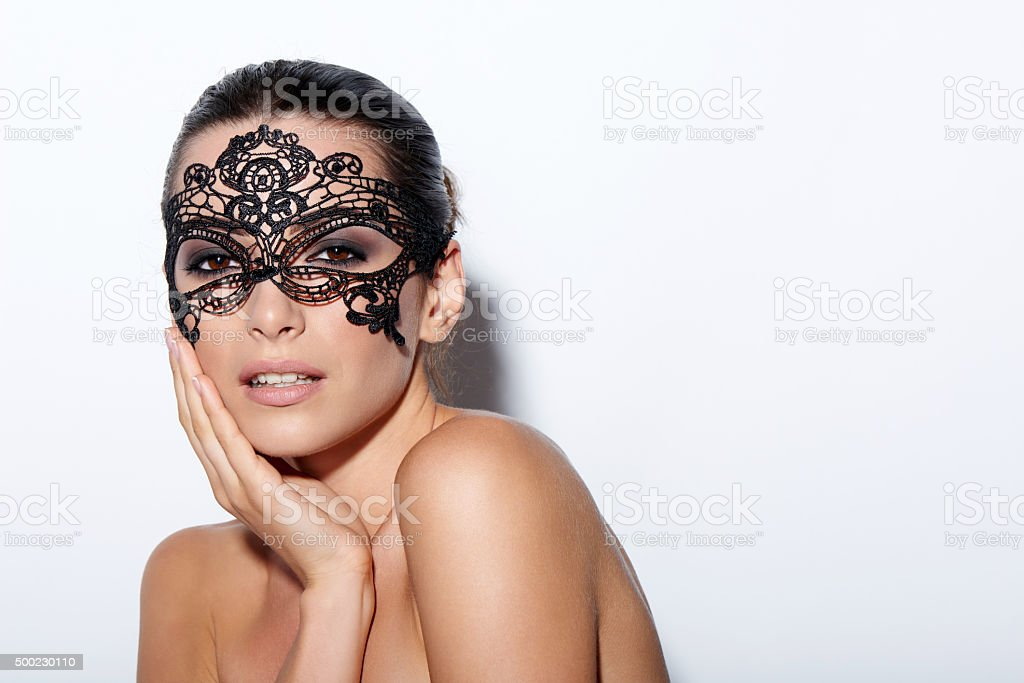 Woman with evening smokey makeup and black lace mask stock photo