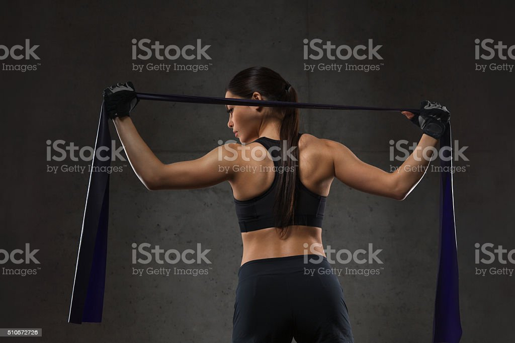 woman with expander exercising in gym stock photo