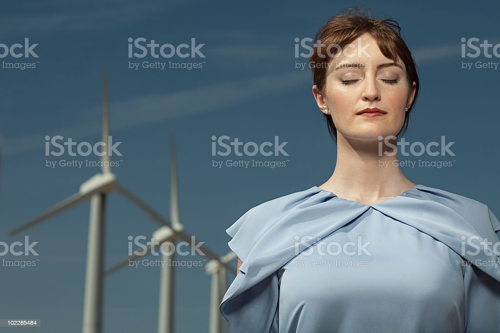 Woman with eyes closed at wind farm royalty-free stock photo