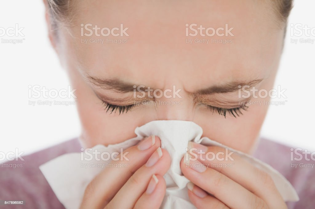 Woman with eyes closed blowing her nose stock photo