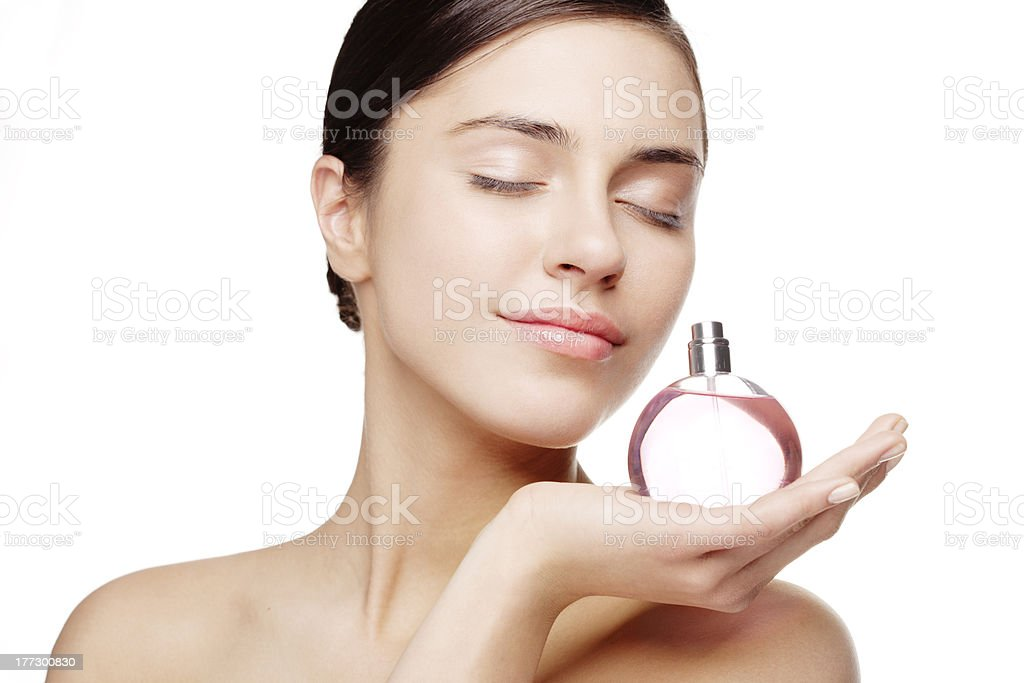Woman with eyes closed smelling a round pink perfume bottle stock photo
