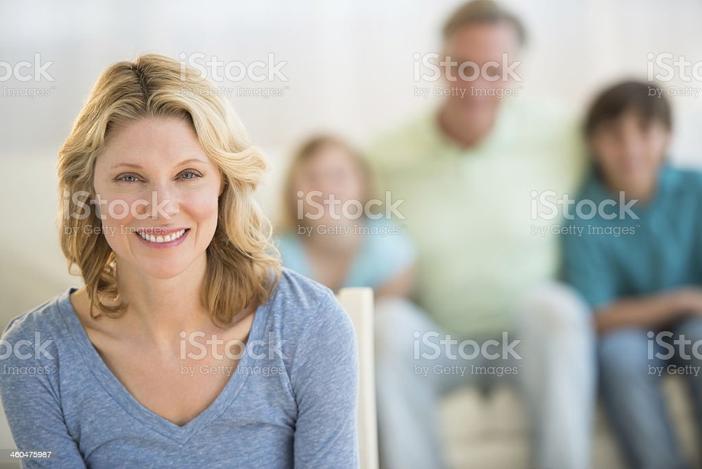 Woman With Family Sitting On Sofa In Background At Home stock photo
