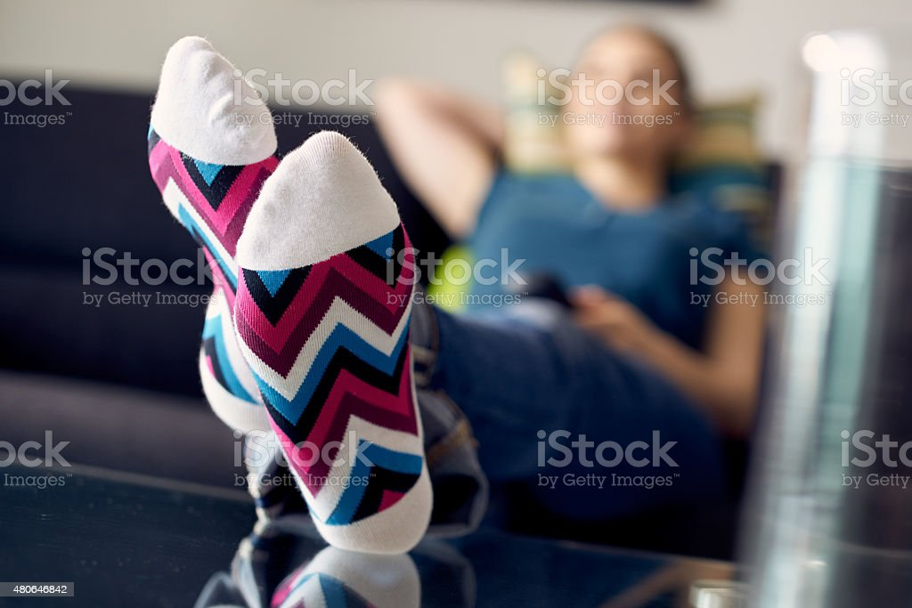 Woman With Feet On Table Watching Film TV At Home stock photo