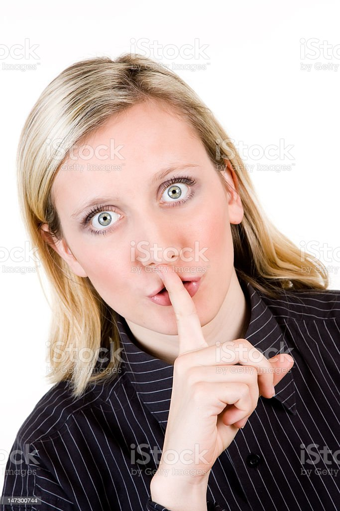 Woman with finger to lips stock photo