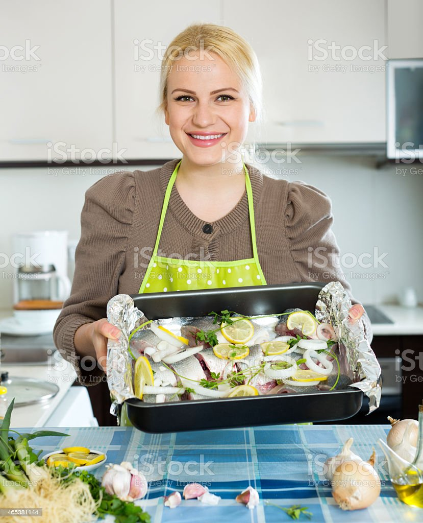 woman with fish in pan stock photo