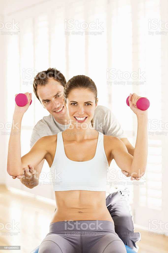 Woman With Fitness Trainer Exercising In Gym royalty-free stock photo