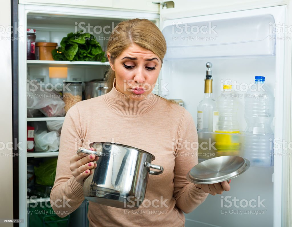 Woman with foul food at kitchen stock photo