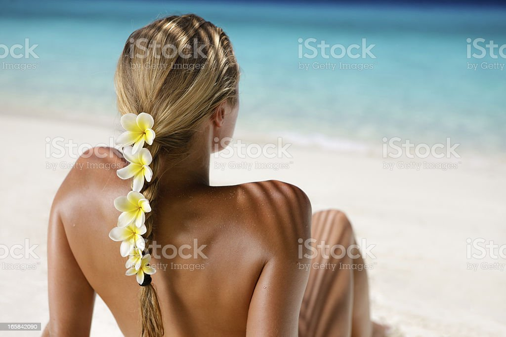 woman with frangipani in hair sunbathing at the Caribbean beach stock photo