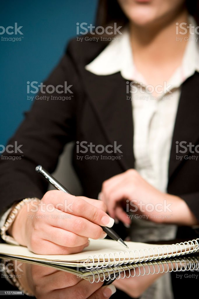 Woman with french manicure in a business suit taking notes stock photo